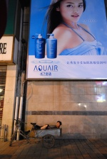 China, The many faces of Beijing  A worker takes a nap under the model's sexy glance on the gigantic advertisement at the central commercial street Wang Fu Jing  © Maro Kouri