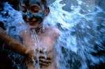 Greece, Peloponissos, Ilia province. At Killini thermal springs an Italian little tourist enjoys the healing earth and water, seems like an angel that flies with his father tender touch.