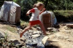 Greek Spas, Smokovo area:A girl jumps over stream waiting her grandmother who takes a warm & natural spring bath full of sulphur, into the handmade shanty.