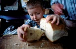 Greece,West Thrace,Rodope mountain.Pomakochoria (Greek Muslim minority. Litlle boy takes a piece of bread.