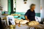 Greece, Amorgos. Old woman makes bread. The photograph of her child's wedding is always on her table. © Maro Kouri