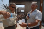 Greece, Peloponese, prefecture of Ileia, Artemida, the village with 26 dead people. Kostas Vlassopolos (l)offers a glass of water to an older man. Kosta's son is the owner of the burnt square's restaurant. © Maro Kouri