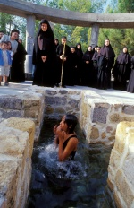 A Buddhist Thailand girl baptizes to Christian at the old-style baptistry of Holy Cross Monastery. Thebes, Central Greece  © Maro Kouri