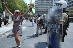 48 hours general strike and demonstations against the Memorandum. Thousands of demonstrators join the Indignant Citizens///Woman with flowers dances in front of the greek Riot Police  © Maro Kouri