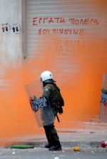 Demonstrations and riots during the second day of the general strike against the second Memorandum///Riot policeman in front of a graffity that writes ''Worker fight. They drink yor blood''  © Maro Kouri