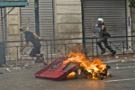 Riots during a rally against plans for new austerity measures///Protester hunted by a riot policeman in  front of a burning garbage bin  © Maro Kouri