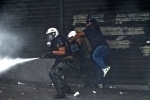 Riots during a rally against plans for new austerity measures///Protesters clash with riot police while they throw teargas  © Maro Kouri
