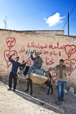 Young men in front of graffity, which referres to the revolution martyrs.   © Maro Kouri