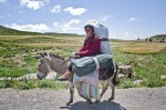Woman traditional dressed with suitcase on a donkey  © Maro Kouri