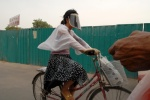 China, 'The many faces of Beijing'. Woman goes to work wearing the typical  huge sunglasses to protect herself from the sunrays that shines through a poison cloud. Every year 300,000 Chinese people die from respiratory problems.   © Maro Kouri