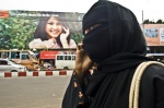 Chittagong, Banglasesh; Contrast between a woman dressed in nigab walking on the street and an advertisement-wallpaper showing a woman dressed in west style, talking also on the mobile phone  © Maro Kouri