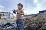October 26, 2011- Botanikos, Athens Greece: Franco is a little boy who works all day and sometimes even during the night in the burnt junk yard where he collects scrap metal in order to sell it  © Maro Kouri