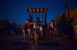 July 5, 2011. Botanikos, Athens, Greece:The night falls in the slum. Instead of going to sleep, the three little Roma boys drive an open truck where they carry  collected cables and scrups in order to sell  © Maro Kouri