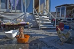 September 16, 2011-Athens, Greece: Baby has a bath into a small plastic basin next to a cock outside his family shanty   © Maro Kouri